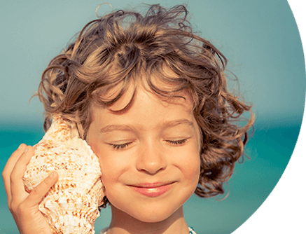 Young child with seashell against ear